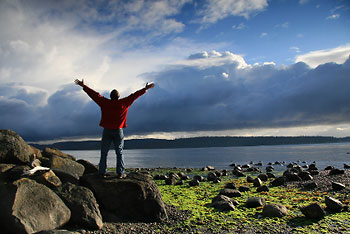 man-on-rocks-beach-arms-raised-to-sky-clouds